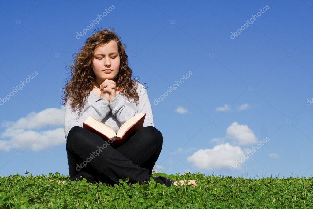 Child or teen praying and reading bible outdoors — Stok fotoğraf #6950125