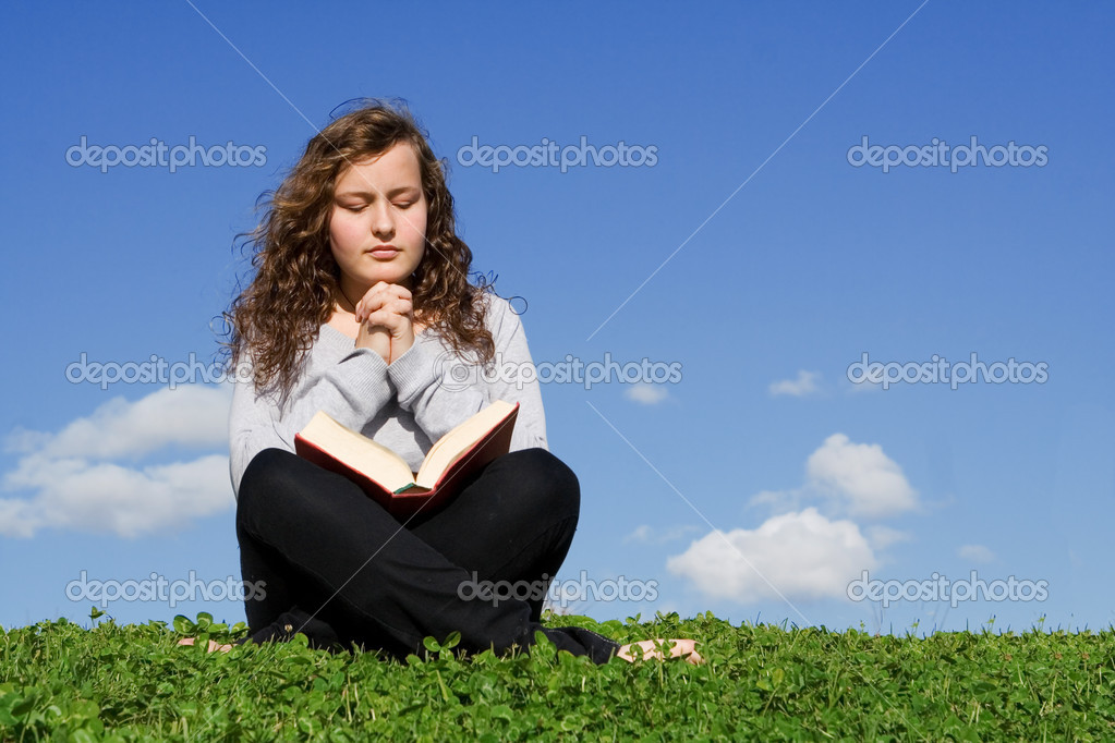 Child or teen praying and reading bible outdoors — Stockfoto #6950125