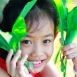 Little girl holding a green vegetable - Stock Photo
