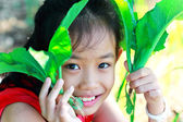 Little girl holding a green vegetable — Stock Photo