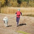 The sports woman with a dog run along coast of the rivers — Stock Photo