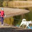 Stock Photo: Sports womwith dog run along coast of rivers