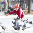 Kid throws bread to the pigeons autumn park — Stock Photo