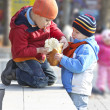 The brothers share the bread for a walk in autumn park — Stock Photo
