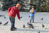 Children fed the pigeons in autumn city park — Stock Photo