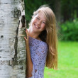 Young girl looks out from the tree — Stock Photo