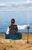 Hombre en traje escocés mirando el mar — Foto de Stock