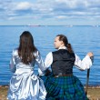 Woman and man in scottish costume near the sea — Stock Photo