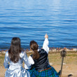 Woman and man in scottish costume sitting near the sea — Stock Photo