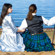 Woman and man in scottish costume sitting near the sea — Stock Photo #7272075