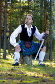 Man in scottish costume with sword and pipe — Stock Photo