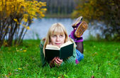 Woman reading the book on the grass — Стоковое фото