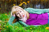 Woman lying on the grass with berry in the mouth — Stock Photo