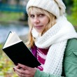 Blond woman in the white cap and scarf with book — Stock Photo