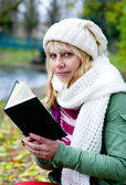 Blond woman in the white cap and scarf with book — Стоковое фото