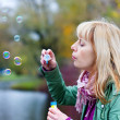 Blond woman with soap bubbles — Stockfoto