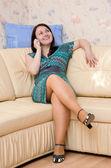Kvinnan pratar på telefon på soffan — Stockfoto