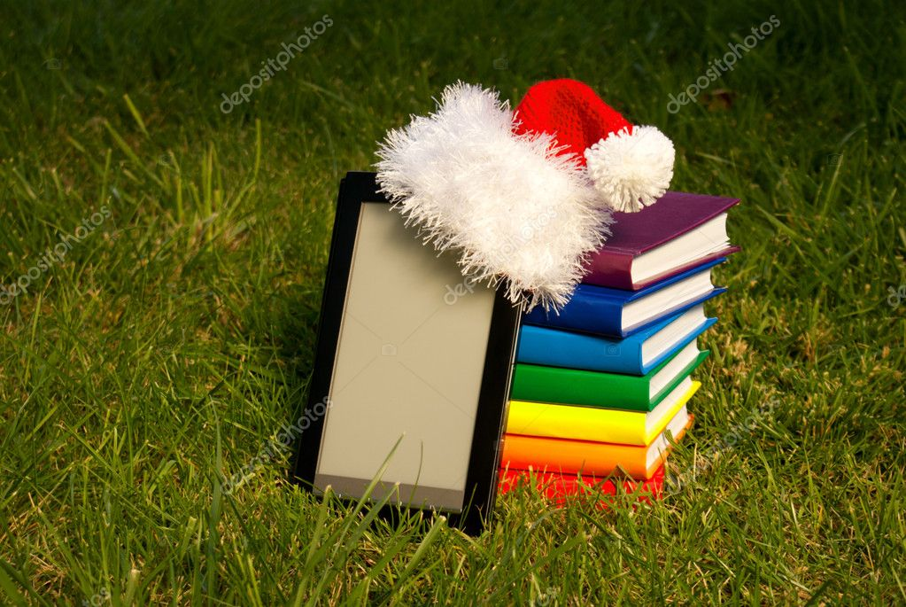 Electronic book reader wearing Santa's hat with stack of books  Stock Photo #6849914