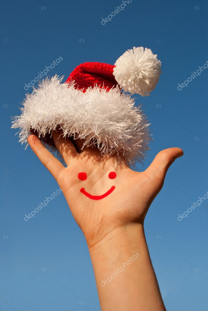 Human's palm with smile on it wearing Santa's hat — Stock Photo #6850007