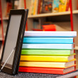 Stack of colorful books with electronic book reader — Стоковая фотография