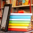 Stock Photo: Stack of colorful books with electronic book reader