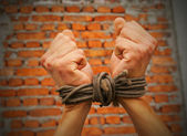 Hands tied up with rope against brick wall — Stock Photo