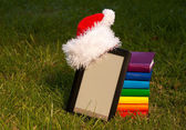 Electronic book reader wearing Santa's hat with stack of books — Foto Stock