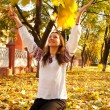 Young lady playing with leaves in a park at fall time — Stock Photo