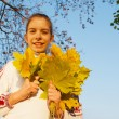 Girl with leaves at fall time — Stock Photo
