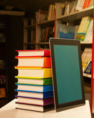 Stack of colorful books and electronic book reader in the book shop — Stock Photo