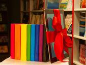 Lector de libros electrónicos atados con cinta roja y la fila de libros — Foto de Stock