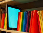 Row of colorful books and electronic book reader on the shelf — Stock Photo