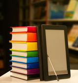 Stack of books with electronic book reader — Stock Photo