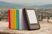 Row of colorful books with electronic book reader — Stock Photo