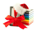 Electronic book reader wearing Santa's hat with stack of books — Stockfoto