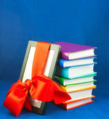 Electronic book reader tied up with red ribbon with stack of books — Stock Photo