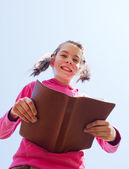 Teen girl reading the Bible against blue sky — Zdjęcie stockowe