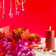 Foto Stock: Christmas gifts and candles over red background