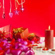 Christmas gifts and candles over red background — ストック写真