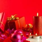 vánoční dárky a svíčky na červeném pozadí — Stock fotografie