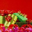 Wrapped boxes with presents against red background — Stock Photo
