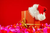 Christmas present with Santa's hat against red background — Foto de Stock