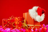Christmas presents with Santa's hat against red background — Stockfoto
