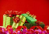 Caixas embrulhadas com presentes contra o fundo vermelho — Fotografia Stock