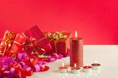 Christmas gifts and candles over red background — Stock Photo