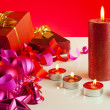 Christmas gifts and four candles over red background — Stock Photo #7920034