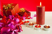 Christmas gifts and four candles over red background — Stock Photo