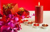рождественские подарки и четыре свечи на красном фоне — Стоковое фото
