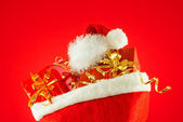 Christmas presents with Santa's hat against red background — Stok fotoğraf