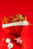 рождественские подарки в мешке красном фоне — Стоковое фото